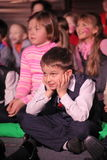 Young theatergoers. children enthusiastically watching children's Christmas puppet show theatre Smeshariki. Stock Image