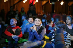 Young theatergoers. children enthusiastically watching children's Christmas puppet show theatre Smeshariki. Royalty Free Stock Photography