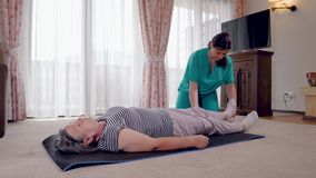Young therapist exercising with older female patient in nursing home stock footage