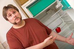 Young thick man in front of a fridge with one paprika inside Royalty Free Stock Images