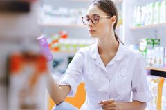 A young thin brown-haired girl with glasses,dressed in a lab coat, crouching,examines medicines on the shelf in a royalty free stock image
