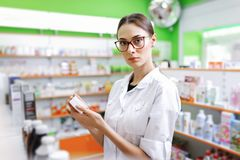 A young thin brown - haired lady with glasses, dressed in a white coat, looks at the camera and holds a small jar in the stock images