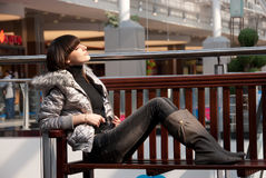 Young thin girl relaxes. On a bench in a mall Stock Image