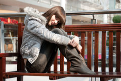 Young thin girl relaxes. On a bench in a mall Royalty Free Stock Photography