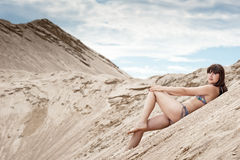 Young thin girl in a swimsuit posing on the sand. In the sky Royalty Free Stock Photo