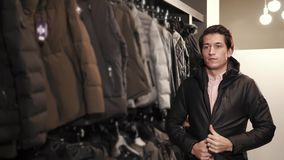 A young man chooses a jacket in a clothing store, he tries on a sample for himself. Young and thin man wears a stylish winter or autumn jacket, people try to stock footage