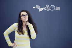Young thinkful woman on blue gray background with finance graphs. Royalty Free Stock Images
