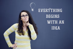 Young thinkful woman on blue gray background with idea sign Royalty Free Stock Images