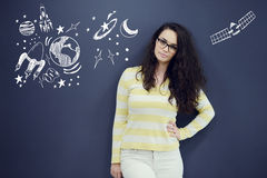 Young thinkful woman on blue gray background with universum icons. Royalty Free Stock Images