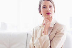 Young thinking businesswoman sitting on sofa looking at camera Royalty Free Stock Photos