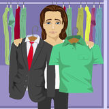 Young thinking man choosing between business suit and shirt in a clothing store. Young thinking man choosing between business suit and green shirt in a clothing Stock Photography