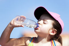 Young girl drinking water. Young thirsty girl drinking water over a clean blue background Royalty Free Stock Image