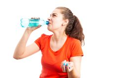 Young thirsty woman hydrating by drinking water from bottle stock photo