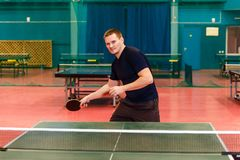 Young thirty-year-old man playing ping pong. Indoors royalty free stock photography