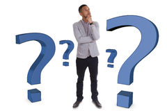 Young thoughtful african american man  surrounded by question ma Stock Photos