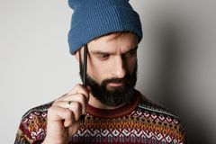 Young thoughtful bearded man in blue beanie thinking about test over empty background. Young thoughtful bearded man in blue beanie thinking about test over stock image