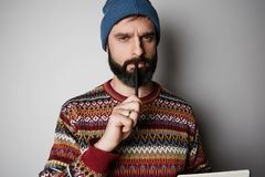 Young thoughtful bearded man in blue beanie thinking about test over empty background. Young thoughtful bearded man in blue beanie thinking about test over stock images