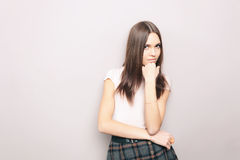 Young thoughtful beautiful brunette woman posing indoors against wall Stock Photo