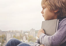 Young thoughtful boy with book sitting and looking through the window Stock Photos