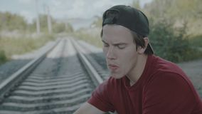 Young thoughtful boy sits on a rail and smokes cigarette. 4K stock video