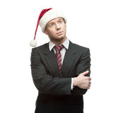 Young thoughtful businessman in santa hat Stock Photos
