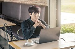 Young thoughtful businessman sitting with his laptop computer at a coffee shop, Royalty Free Stock Photo