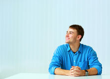 Young thoughtful businessman sitting at the table and looking up Royalty Free Stock Images