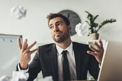 Young thoughtful businessman throwing crumpled papers. At modern office royalty free stock image