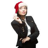 Young thoughtful businesswoman in santa hat standing isolated on Royalty Free Stock Photo