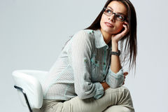 Young thoughtful businesswoman sitting on the chair. On gray background Royalty Free Stock Images