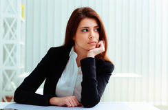 Young thoughtful businesswoman sitting on her workplace Royalty Free Stock Image