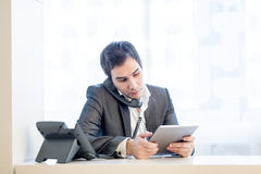 Young thoughtful busy businessman sitting at hiss office desk ta Royalty Free Stock Image