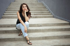 Young thoughtful fashionable brunette woman in black leather jacket posing sitting on concrete stairway Royalty Free Stock Image