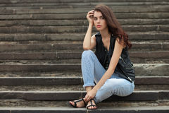 Young thoughtful fashionable brunette woman in black leather jacket posing sitting on park stairway Royalty Free Stock Images