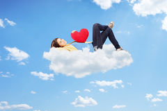 Young thoughtful female holding a heart and lying on clouds. Young thoughtful female holding a red heart and lying on clouds stock photos