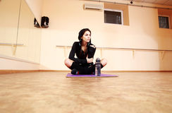 Young thoughtful fit woman sitting on the yoga mat Royalty Free Stock Photo