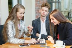 Young thoughtful friends having a chess competition on a cafe background. Friendship concept. Group of teenagers having fun at the cafe and playing a chess game Stock Photo