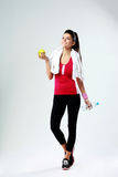 Young thoughtful happy sport woman with apple and bottle of water Royalty Free Stock Photo
