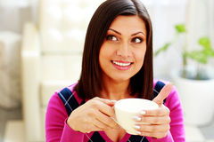 Young thoughtful happy woman holding cup of coffee Royalty Free Stock Photo