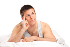 A young thoughtful male lying on a bed Stock Images