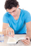 Young thoughtful man in blue t-shirt with glasses sitting at ta Royalty Free Stock Images
