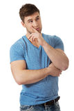 Young thoughtful man with finger under chin. Royalty Free Stock Image