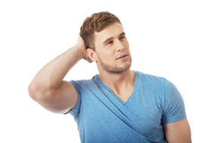 Young thoughtful man with hand behind head. Stock Images