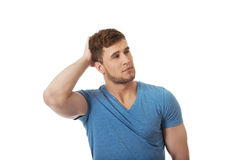 Young thoughtful man with hand behind head. Royalty Free Stock Images
