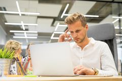 Man in office working on laptop. Young thoughtful man in office working on laptop Stock Photos