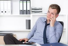 Young thoughtful man is sitting at the desk in the office Stock Photo