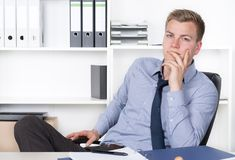Young thoughtful man is sitting at the desk in the office Royalty Free Stock Images