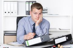 Young thoughtful man is sitting in front of many files Stock Photo