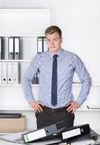 Young thoughtful man is standing in front of many files Royalty Free Stock Photography
