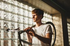 Young thoughtful man standing and holding bicycle that leaning on his shoulder dreamily looking aside. Portrait of boy. Young thoughtful man standing and holding Royalty Free Stock Image